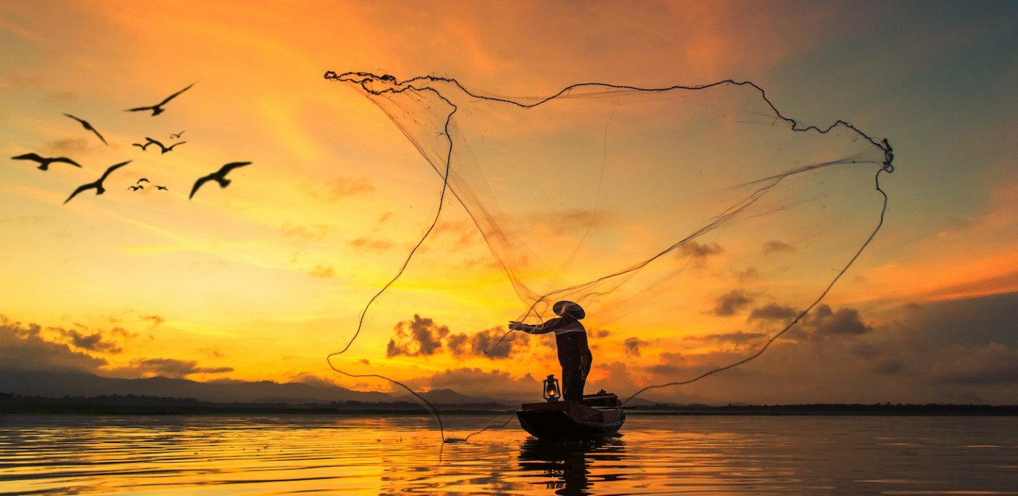 Fisherman in Southeast Asia casting his net